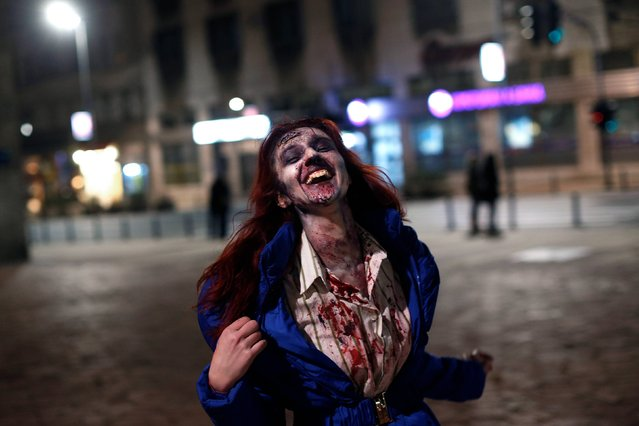 "A girl dressed as a zombie takes part in a ""Zombie Walk"" in central Belgrade, Serbia, Sunday, October 26, 2014. Around a hundred people in masks and make up paraded in the streets of the Serbian capital on Sunday to promote a local science fiction film festival. (Photo by Marko Drobnjakovic/AP Photo)"