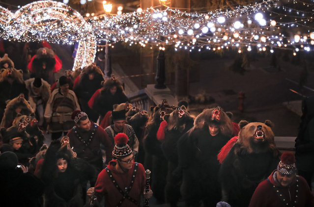 In this Thursday, December 28, 2017, picture people wearing a bear fur costumes walk under Christmas decorations in Piatra Neamt, Romania. (Photo by Vadim Ghirda/AP Photo)