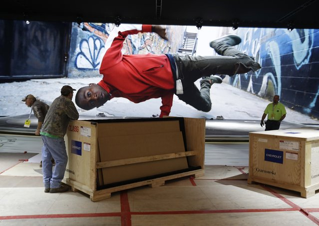 Installation continues at General Motors' showplace at the North American International Auto Show, as a video plays in the background, Friday, January 12, 2018, in Detroit. The show opens to the media on Monday, Jan. 15. (Photo by Carlos Osorio/AP Photo)