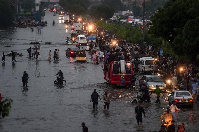 Motorists and pedestrians wade through a flooded street after heavy monsoon rains in the Pakistan's port city of Karachi on August 21, 2020. (Photo by Asif Hassan/AFP Photo)