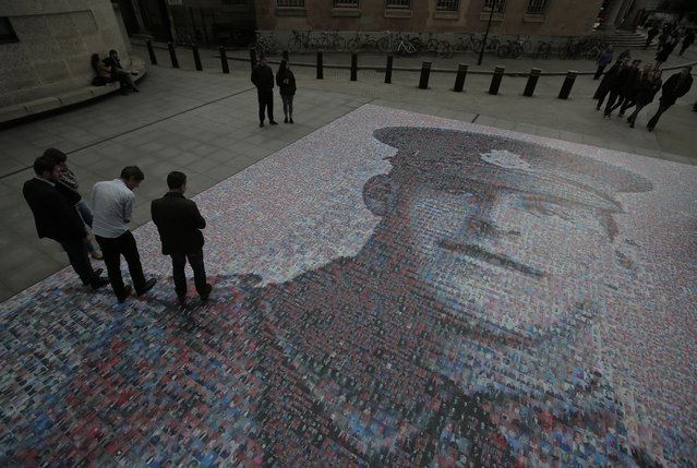 People walk on and around a digital mosaic of photographs of people, depicting British Army private James Ernest Beaney, killed during World War One, outside the BBC headquarters in central London, Friday, November 7, 2014. Created by artist Helen Marshall, the portrait created by using more than 30,000 images, depicts Beaney, who was serving in France, when he was killed on August 8, 1916. (Photo by AP Photo)