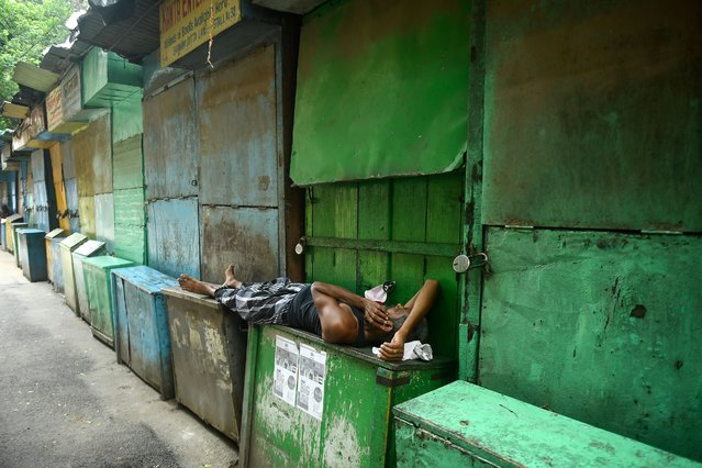 A man rests in front of closed book stalls during a day long state-imposed lockdown as a preventive measure against the surge in Covid-19 coronavirus cases, in Kolkata on August 31, 2020. (Photo by Dibyangshu Sarkar/AFP Photo)