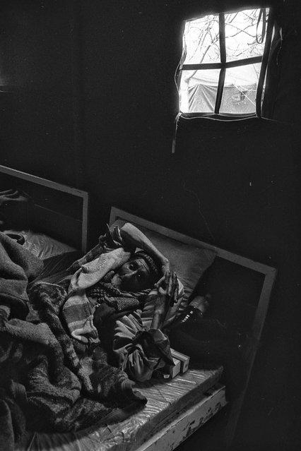 An Iraqi Kurdish refugee lies in a medical tent in Cukurca refugee camp in Turkey, April 8, 1991. (Photo by Srdjan Zivulovic/Reuters)