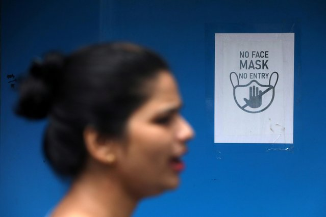 A woman walks past a sign put up outside a shop at a market, amidst the spread of the coronavirus disease (COVID-19) in Mumbai, India September 6, 2020. (Photo by Francis Mascarenhas/Reuters)