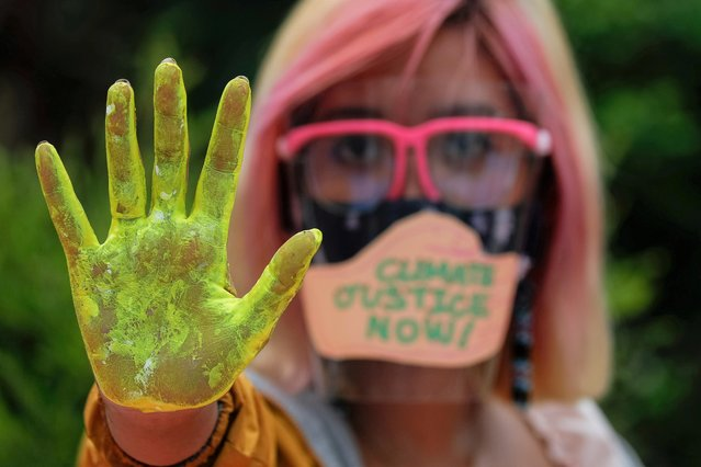 """A Filipino climate activist wearing a face shield with the words """"Climate Justice Now"""" poses showing her hand as part of global climate change protests, in Quezon City, Metro Manila, Philippines on September 25, 2020. (Photo by Eloisa Lopez/Reuters)"""