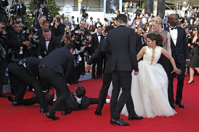 """A man is arrested by security as he tries to slip under the dress of actress America Ferrera (3rd R) in Cannes in this May 16, 2014 file photo. I was covering the stars' red-carpet arrival for the film screening of """"How to Train Your Dragon 2"""". (Photo and caption by Benoit Tessier/Reuters)"""
