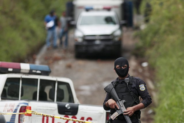 A policeman stands guard at a crime scene where four men were executed in the town of Cojutepeque October 21, 2015. Four suspected gang members were killed by armed men after they were taken from their homes during the night, by men dressed as policemen and executed. The victims were linked to the murder of a police agent in September, according to local media. (Photo by Jose Cabezas/Reuters)