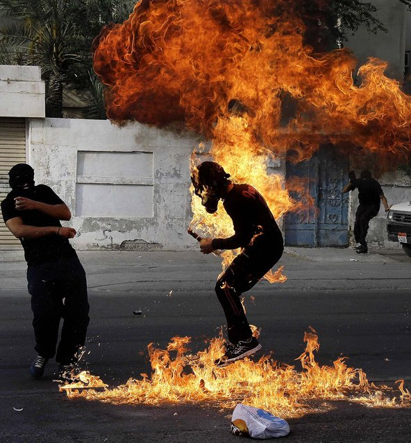 "An anti-government protester is engulfed in flames after a shot fired by police hit the petrol bomb he was preparing to throw during clashes in Sanabis, Bahrain, on March 14, 2013. Protests and clashes erupted nationwide as government opponents called a ""Dignity Strike"",  blocking roads, closing shops, protesting and staying home from work and school. (Photo by Hasan Jamali/Associated Press)"