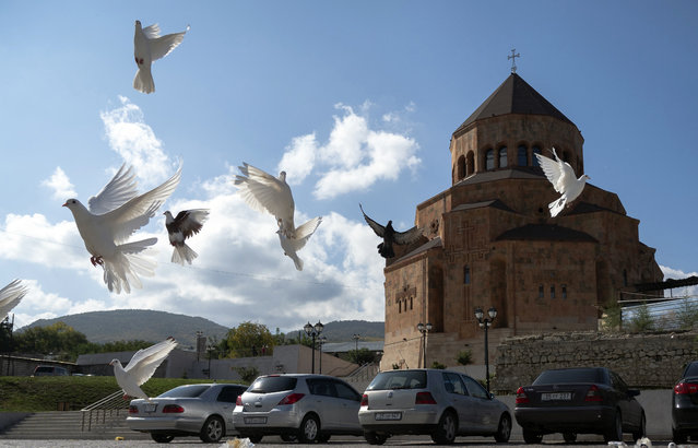 Pigeons fly near Holy Mother of God Cathedral in Stepanakert during a military conflict in the separatist region of Nagorno-Karabakh, Friday, October 9, 2020. Armenia and Azerbaijan say they have agreed to a cease-fire in Nagorno-Karbakh starting at noon Saturday. (Photo by AP Photo/Stringer)
