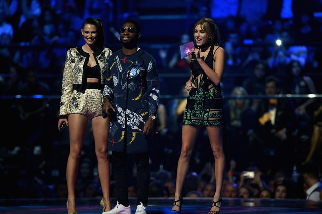 (L-R) Bianca Balti, Tinie Tempah and Hailey Baldwin present the award for Best Video on stage during the MTV EMA's 2015 at the Mediolanum Forum on October 25, 2015 in Milan, Italy. (Photo by Brian Rasic/Getty Images for MTV)