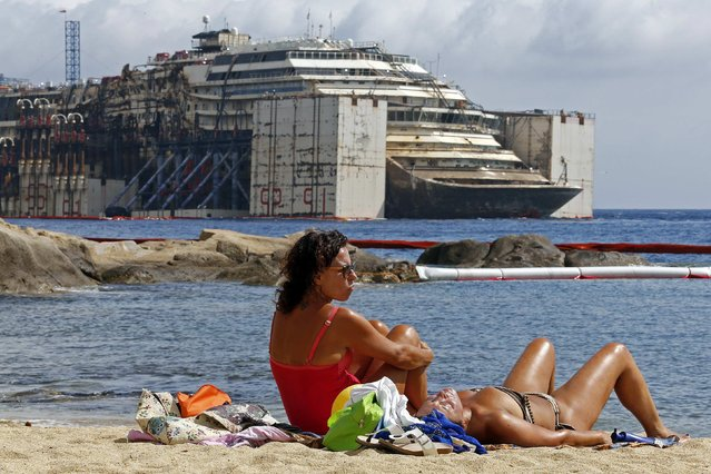 People sunbathe as the Costa Concordia cruise liner is seen during its refloating operation at Giglio harbour, in this July 21, 2014 file photo. (Photo by Giampiero Sposito/Reuters)