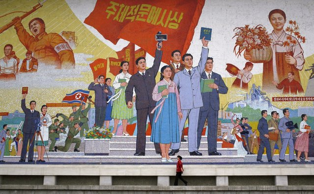In this September 18, 2012 photo, a North Korean woman walks past a huge picture at the Korean Film Studio in Pyongyang, North Korea. (Photo by Vincent Yu/AP Photo)