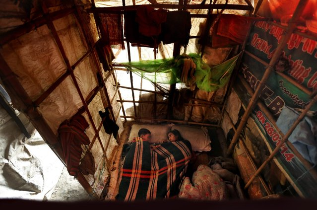 In this November 10, 2014 photo, Murshida, 12, right, looks at her brother Shahid-ul, 7, lying ill on a bed inside their rented shanty on the outskirts of New Delhi, India. The children live with their mother, a rag picker, and spend their day at a landfill picking through other people's garbage to find salvageable bits to resell or recycle. (Photo by Altaf Qadri/AP Photo)