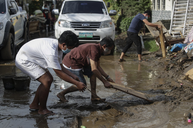 Residents use wood to clear out a mud-covered road after floodwaters caused by Typhoon Goni rose inside their village in Batangas city, Batangas province, south of Manila, Philippines on Monday, November 2, 2020. (Photo by Aaron Favila/AP Photo)