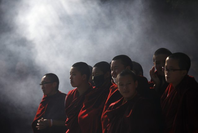 Smoke rise from the burning incense as Tibetan nuns take part in an event organised by the Tibetan Refugee Community in Nepal commemorating the 25th Anniversary of the Nobel Peace Prize conferment to exiled Tibetan spiritual leader Dalai Lama and the 66th International Human Rights Day in Kathmandu December 10, 2014. (Photo by Navesh Chitrakar/Reuters)