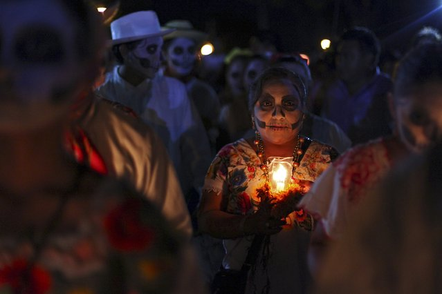"A woman, with her face painted as a skull, holds a candle while taking part in a traditional parade called ""Paseo de las Animas"", or Parade of Souls, as part of Day of the Dead celebrations in Merida, Mexico, October 31, 2015. (Photo by Lorenzo Hernandez/Reuters)"