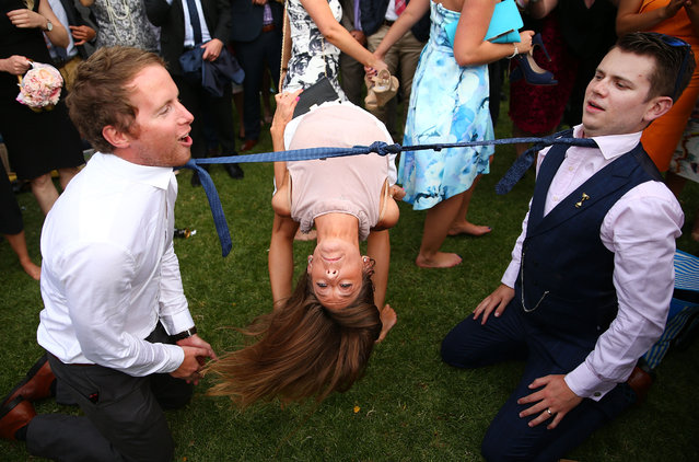 A woman bends backwards between two racegoers who have their ties tied together as racegoers play a game of Limbo following 2015 Melbourne Cup Day at Flemington Racecourse on November 3, 2015 in Melbourne, Australia. (Photo by Scott Barbour/Getty Images)