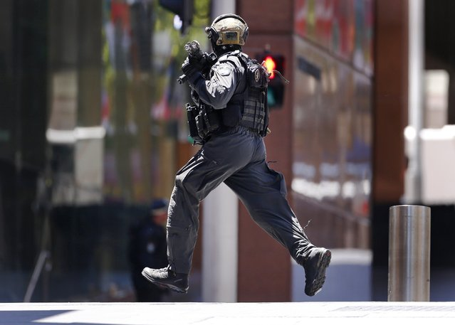 A police officer runs across Martin Place near Lindt cafe, where hostages are being held, in central Sydney December 15, 2014. (Photo by David Gray/Reuters)