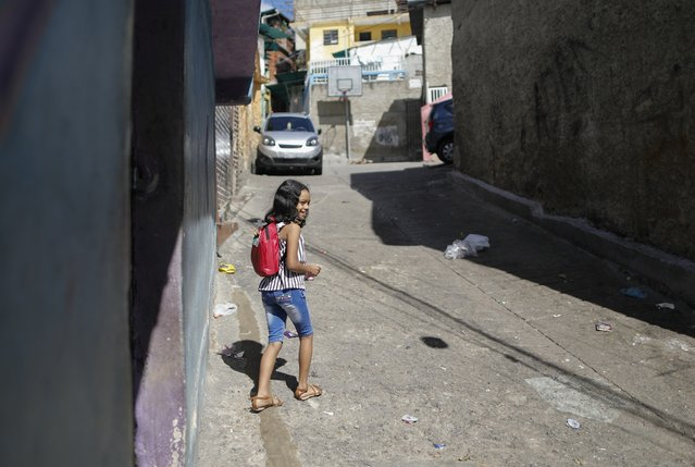 "Jenashly Matos walks back home after attending a tutorial class at a soup kitchen run by the Venezuelan charity, ""Feed the Solidarity"", in the El Atlantico neighborhood of Caracas, Venezuela, Monday, November 2, 2020. ""If I'm not learning, I feel like I'm nobody in life"", said the 9-year-old. ""That's why I come here"". (Photo by Ariana Cubillos/AP Photo)"