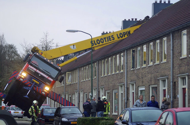 A crane which crashed into the roof of a house is seen following an unusual marriage proposal by a man who wished to be lifted in front of the bedroom window of his girlfriend to ask for her hand in marriage, in the central Dutch town of IJsselstein, Saturday December 13, 2014. No people were injured in the accident, the groom-to-be jumped to safety without injuries and his girlfriend accepted to marry him, according to local Dutch media. (Photo by AP Photo/AS Media)