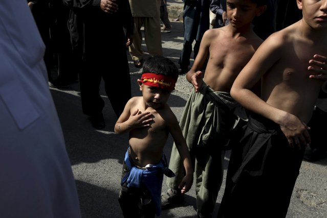A Pakistani Shi'ite Muslim boy beats his chest while taking part in a Muharram procession with others ahead of Ashura in Islamabad, Pakistan, October 23, 2015. Ashura, which falls on the 10th day of the Islamic month of Muharram, commemorates the death of Imam Hussein, grandson of Prophet Mohammad, who was killed in the seventh century battle of Kerbala. (Photo by Faisal Mahmood/Reuters)