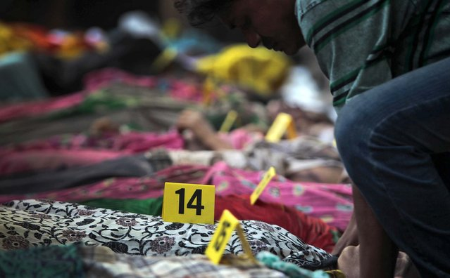 Bodies of victims lie numbered in a row after the building collapse on Wednesday. (Photo by A. M. Ahad/Associated Press)