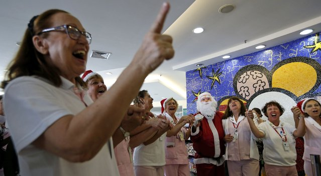 A man dressed as Santa Claus dances with nurses at the Cancer Institute in Sao Paulo December 19, 2014. (Photo by Paulo Whitaker/Reuters)