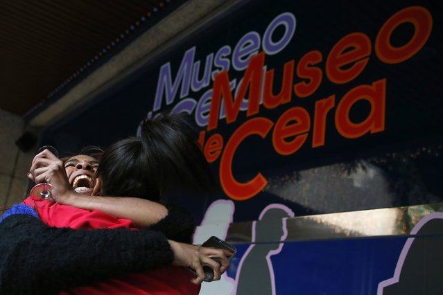 """Madrid Wax Museum's worker Noemi Vazquez (L) and her sister Maria celebrate having won a portion of the Spain's Christmas Lottery """"El Gordo"""" in Madrid December 22, 2014. (Photo by Juan Medina/Reuters)"""