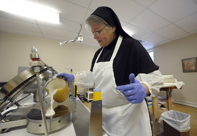Sister Rebecca Leis pours low-gluten alter bread batter into a machine that bakes the thin bread at the Benedictine Sisters of Perpetual Adoration monastery in Clyde, Missouri, December 18, 2014. The Sisters have made communion wafers since 1910 and began making a low-gluten version in 2003 and have gone from 143 customers in 2004 to more than 11,000 customers from around the world. (Photo by Dave Kaup/Reuters)