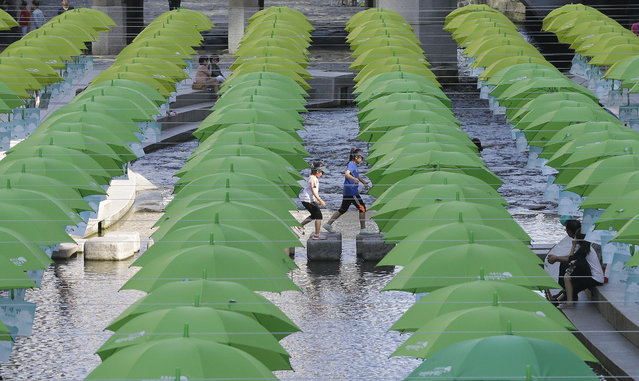 Children walk under umbrellas on display over Cheonggye stream during a campaign to raise donations to help underprivileged children in Seoul, South Korea, Tuesday, October 4, 2016. (Photo by Ahn Young-joon/AP Photo)