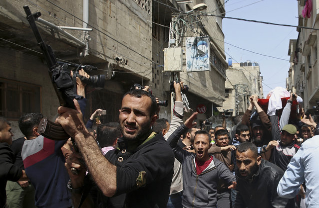 Relatives carry the body of Mohammed Hajeleh, 30, who was killed early Thursday morning by an Israeli airstrike, while others fire their weapons in the air, during his funeral, in front of his family house in Gaza City, Thursday, April 12, 2018. The Israeli military said it bombed a Hamas military target in the Gaza Strip hours after an explosive device detonated near an Israeli army vehicle on the border. (AP Photo/Adel Hana)