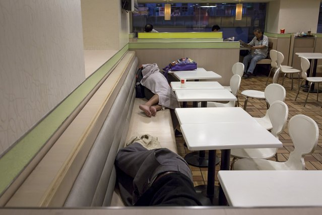 Men sleep at a 24-hour McDonald's restaurant as people read newspapers behind them (R), in Hong Kong, China November 11, 2015. (Photo by Tyrone Siu/Reuters)