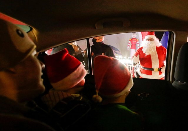 Children greet a person dressed as Santa Claus from inside a vehicle in a drive-thru christmas village, amid the coronavirus disease (COVID-19) outbreak, in Ciudad Juarez, Mexico on December 3, 2020. (Photo by Jose Luis Gonzalez/Reuters)