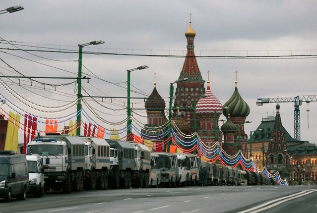 Police trucks line up on a bridge during a major protest rally in Moscow, with St. Basil Cathedral in the background, Russia, Monday, May 6, 2013. Up to 20,000 Russian opposition supporters gathered for a protest on Monday, venting anger against the Kremlin and demanding the release of political prisoners. The protest came exactly one year after a demonstration a day before President Vladimir Putin's third presidential inauguration on the same square near the Kremlin ended in violent clashes between demonstrators and police. (AP Photo/Mikhail Metzel)