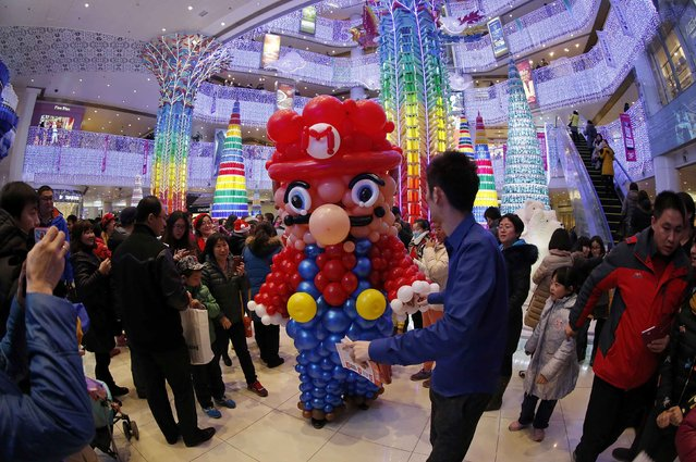 A staff wearing a Super Mario Brother costume made of balloons is led by his colleague as they walk among customers during a promotional event to celebrate Christmas, at a department store in Beijing, December 24, 2014. (Photo by Barry Huang/Reuters)