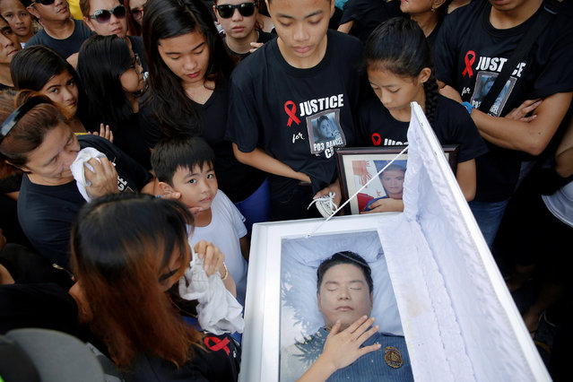 The wife of Rancel Cruz, a police officer killed by an unknown gunman earlier this month, touches the glass covering his coffin, during the funeral in Manila, Philippines October 22, 2016. (Photo by Damir Sagolj/Reuters)