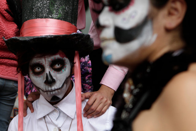 Angel Paz, dressed as a calavera, waits with family for the start of the Gran Procession of the Catrinas, to mark the upcoming Day of the Dead holiday, in Mexico City, Sunday, October 23 2016. (Photo by Anita Baca/AP Photo)