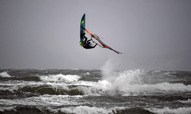 A windsurfer performs a trick at Barassie Beach in Troon, on the west coast of Scotland on Boxing Day, December 26, 2020 as Storm Bella brings rain and high winds to the UK. (Photo by Andy Buchanan/AFP Photo)