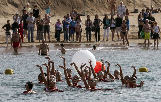 """Swimmers peform the synchro routine """"A Sea of Happiness"""" to mark New Year in Las Canteras beach, Canary Islands, Spain, 31 December 2014. Some 50 swimmers took part in the performance directed by Spanish olympic medal winner Paola Tirados (unseen).  (Photo by Angel Medina G./EPA)"""