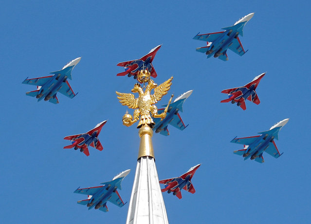 Russian army MiG-29 jet fighters of the Strizhi (Swifts) and Su-30 jet fighters of the Russkiye Vityazi (Russian Knights) aerobatic teams fly in formation during the Victory Day parade, marking the 73rd anniversary of the victory over Nazi Germany in World War Two, in central Moscow, Russia May 9, 2018. (Photo by Maxim Shemetov/Reuters)