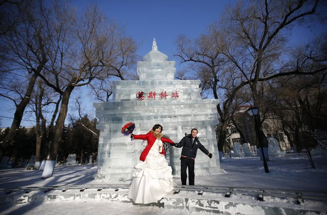 A newly wed couple poses in front of an ice sculpture for their wedding photographs after their group wedding ceremony which was held as part of the Harbin International Ice and Snow Festival in the northern city of Harbin, Heilongjiang province January 6, 2015. (Photo by Kim Kyung-Hoon/Reuters)
