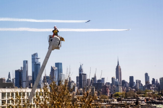 "A PSE&G utility worker watches the Navy's Blue Angels and the Air Force's Thunderbirds conduct ""a collaborative salute"" to honor those battling the COVID-19 pandemic with a flyover of New York and New Jersey, Tuesday, April 28, 2020, in this view from Jersey City, N.J. (Photo by Charles Sykes/Invision/AP Photo)"