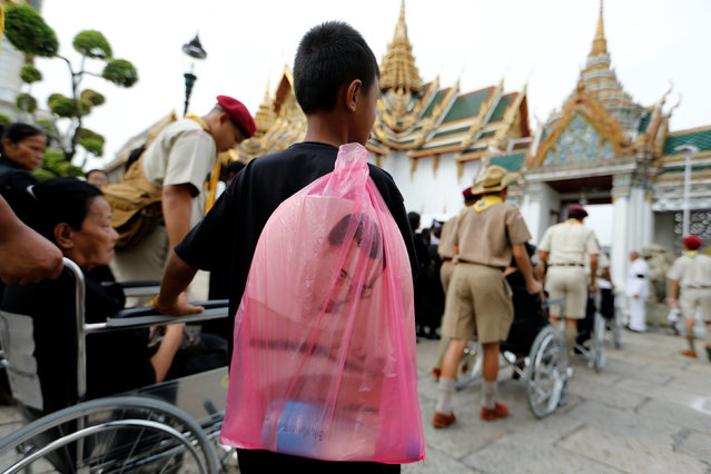 A mourner holds a bag with a picture of Thailand's late King Bhumibol Adulyadej while lining up to enter the Throne Hall for the first time to pay his respects in front of the golden urn of the late king in Bangkok, Thailand, October 29, 2016. (Photo by Jorge Silva/Reuters)