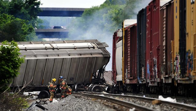 A fire burns at the site of a CSX freight train derailment in Rosedale, Maryland,, on May 28, 2013, where fire officials say the train crashed into a trash truck, causing an explosion that rattled homes at least a half-mile away and collapsed nearby buildings, setting them on fire. (Photo by Kim Hairston/Baltimore Sun/MCT)