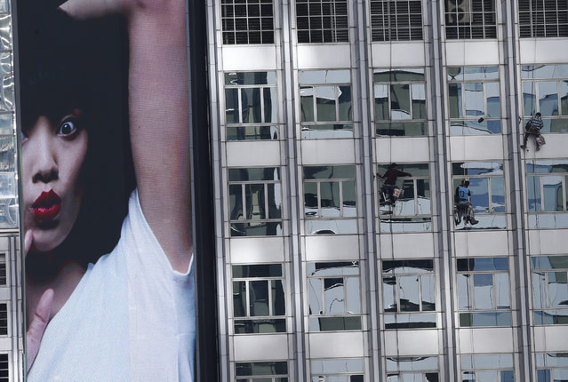 Window cleaners operate on a high rise building next to a digital advertisement screen at a business district in Bangkok, Thailand, 25 November 2015. The Central Bank of Thailand maintained its key interest rate unchanged at 1.5 percent while waiting to see the results of the government stimulus package which is expected to help boost local demand in the last quarter of 2015 and an overall rebound in the country's economy in 2016. (Photo by Narong Sangnak/EPA)