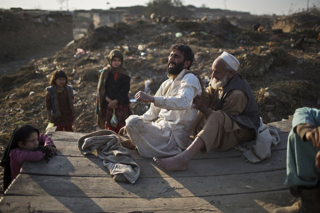 A man who suffers from back pain reacts while having a massage by an elderly Afghan refugee man on a roadside on the outskirts of Islamabad, Pakistan, Thursday, January 1, 2015. (Photo by Muhammed Muheisen/AP Photo)