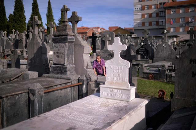 A woman sits on a grave on All Saints' Day at Derio cemetery near Bilbao, Spain, November 1, 2016. (Photo by Vincent West/Reuters)