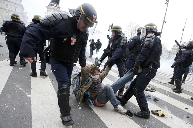 French CRS riot police apprehend a demonstrator during clashes near the Place de la Republique after the cancellation of a planned climate march following shootings in the French capital, ahead of the World Climate Change Conference 2015 (COP21), in Paris, France, November 29, 2015. (Photo by Eric Gaillard/Reuters)