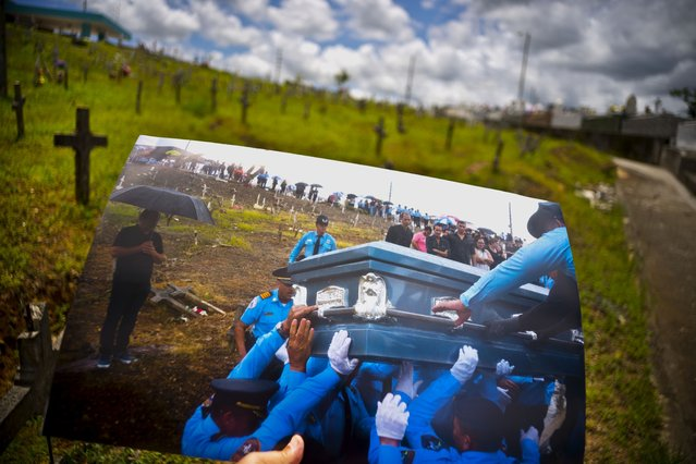 A printed photo taken on September 29, 2017 showing police lifting the coffin of officer Luis Angel Gonzalez Lorenzo, who was killed during the passage of Hurricane Maria when he tried to cross a river in his car, is shown at the same cemetery in Aguada, Puerto Rico, May 31, 2018. The local police force of Aguadilla and Aguada lacks about a dozen officers since the storm, due to resignations and retirements. The U.S. territory's bankruptcy has frozen promotions, salaries, new hires and some police academies have even closed. (Photo by Ramon Espinosa/AP Photo)