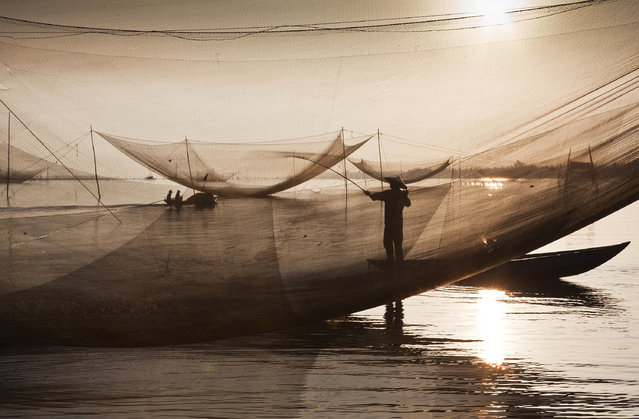 """Waterworlds"". Fishermen's work in the early hours across Vietnam. The work often starts in the night and lasts untill the next morning. Over several weeks I attended a few fishermen to observe their daily work and procedure of catching fish. Location: Hoi An, Vietnam. (Photo and caption by Kostas Maros/National Geographic Traveler Photo Contest)"